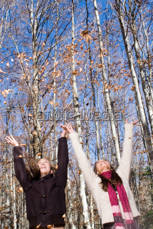 2 young woman throwing leaf in