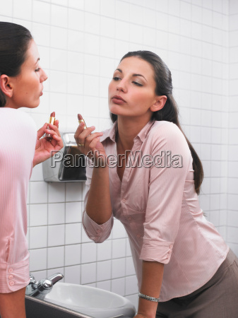 woman reflected in office washroom mirror