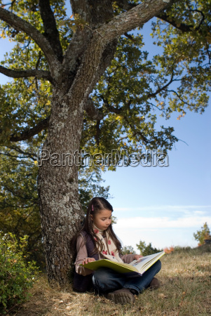 young girl leaning against a tree