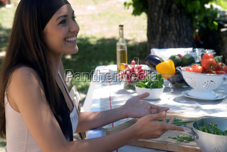 young woman preparing fresh green beans