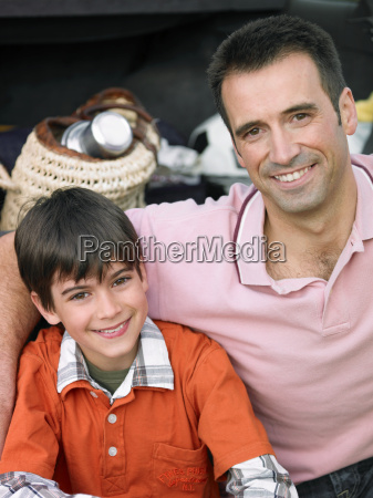 father sitting with arm around son