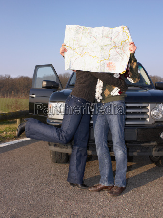 couple behind map