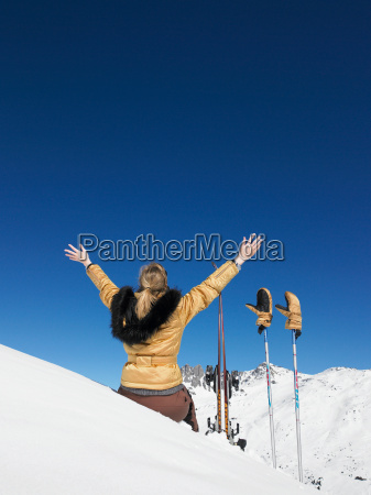 young woman skier admiring mountain view