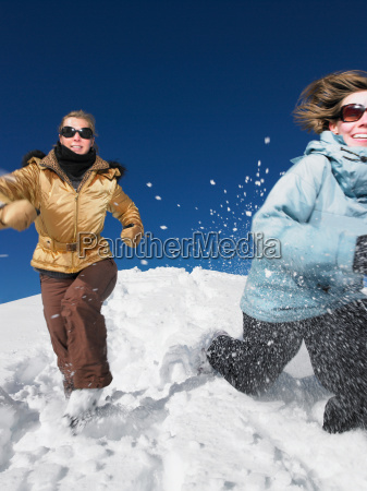 young women running in snow
