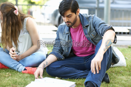male student sitting working on college