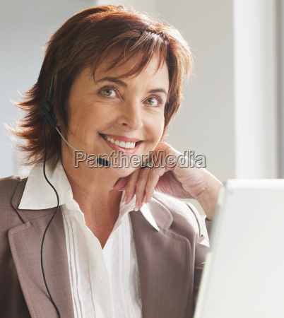 senior woman with headset at laptop