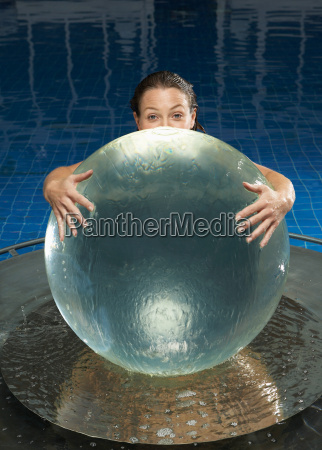 woman with water globe in pool