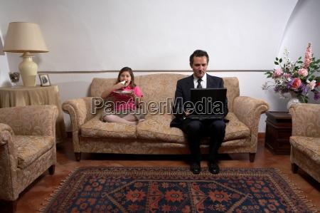 man using laptop with daughter