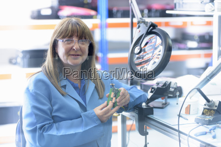 female worker soldering electronic parts in