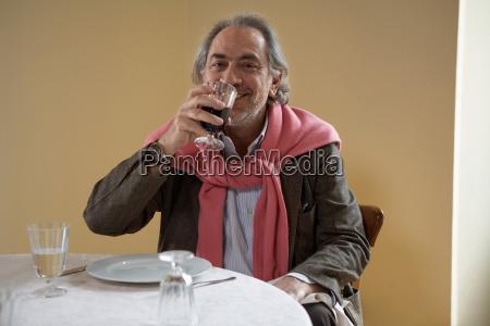 senior adult man enjoying wine at