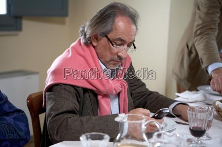 mature man text messaging at dinner
