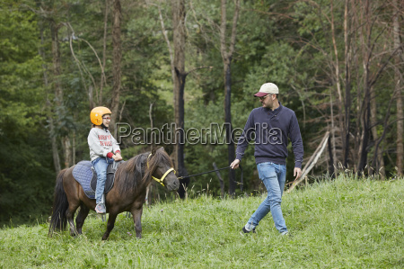 father with daughter riding pony valle