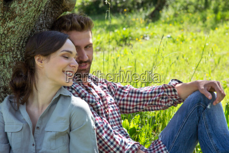young couple sitting leaning against tree