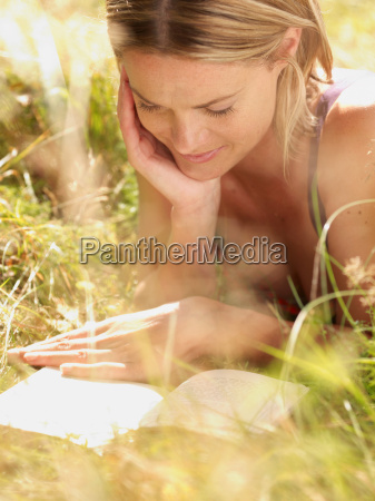 woman lying in grass reading a