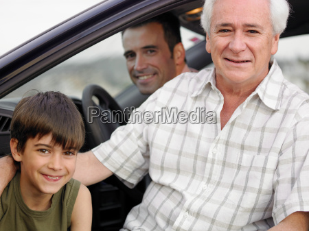 boy sitting with father and grandfather