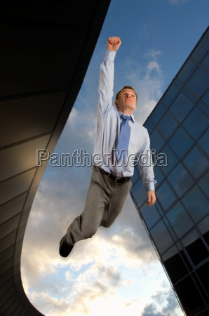 businessman flying overtop of the city