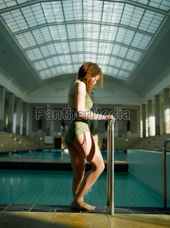woman standing by swimming pool foot