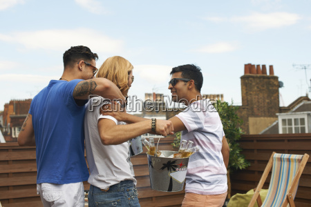 three male friends carrying ice bucket