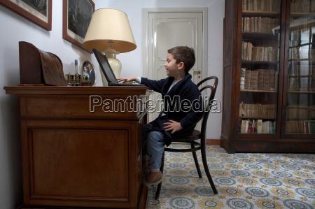boy sitting at desk using laptop