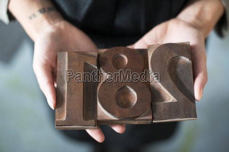 womans hands holding traditional letterpress numerals