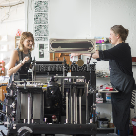 two women working with traditional letterpress