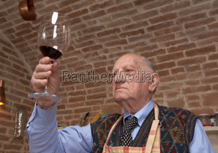 senior adult man looking at wine