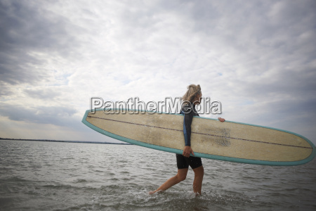 senior woman walking from sea carrying