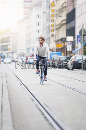 young man riding bicycle in road
