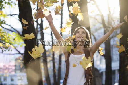 mid adult woman throwing autumn leaves