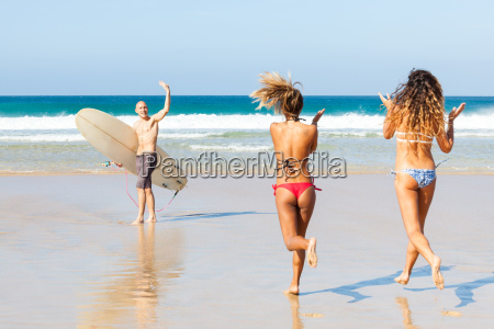 male surfer waving to female friends