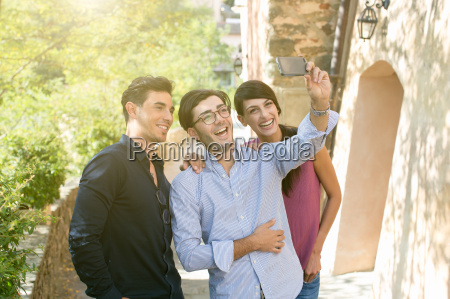 three young adult friends taking smartphone