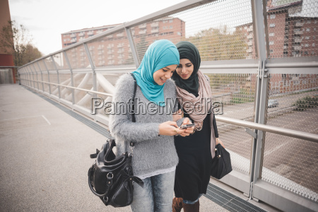 two female friends on footbridge reading