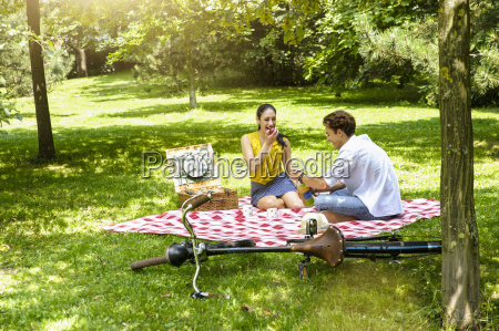 young couple sitting eating picnic on