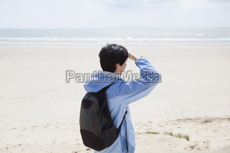 mid adult woman on beach shielding