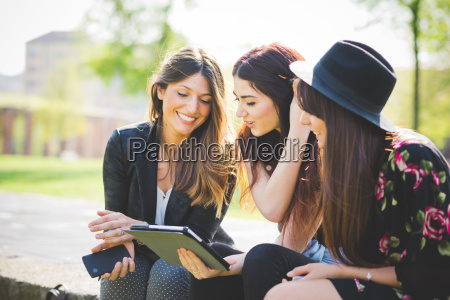 three young female friends sharing update