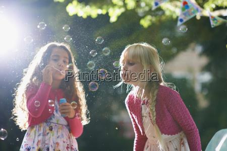 two girls blowing bubbles in sunlit