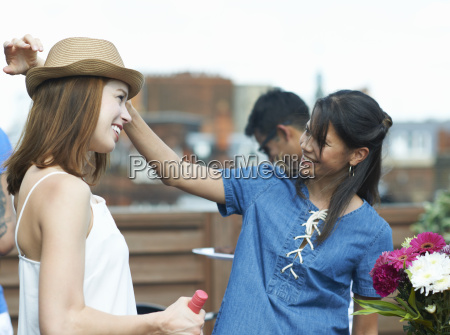 female friends chatting at rooftop party