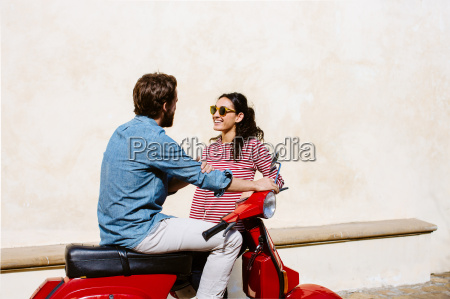 young couple on moped chatting florence