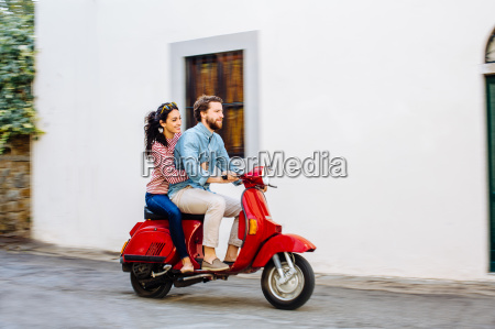 young couple riding moped on village