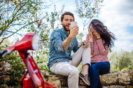 young couple sitting on olive grove