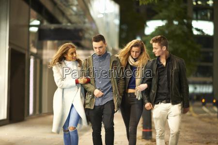 two young couples strolling arm in