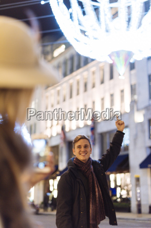 young couple pointing to xmas lights