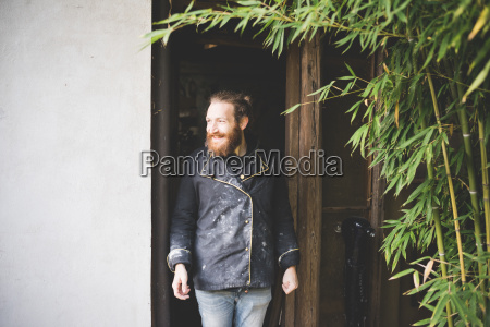 bearded man standing in doorway looking