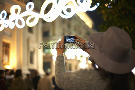 woman photographing decorative lights in street
