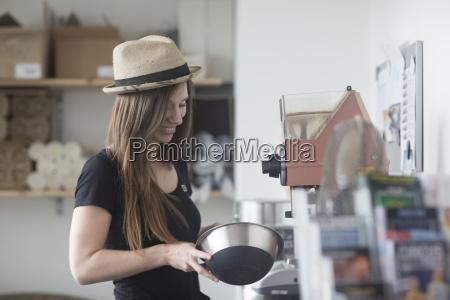 young female waitress preparing food behind