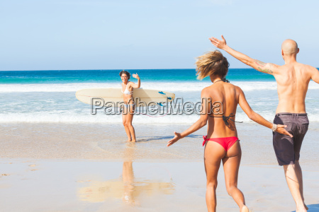 young female surfer waving to friends