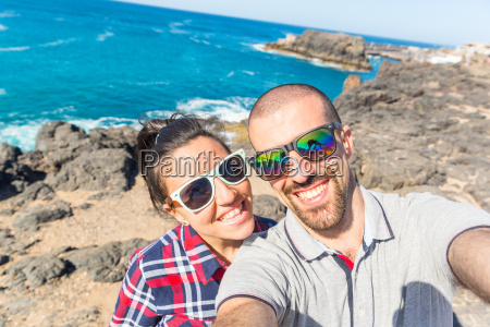 young couple taking smartphone selfie at