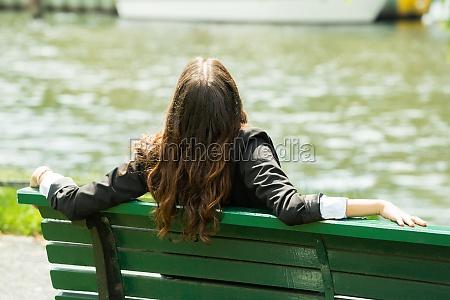 geschaeftsfrau die auf bank sitzt