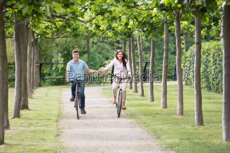 the happy couple cycling in park