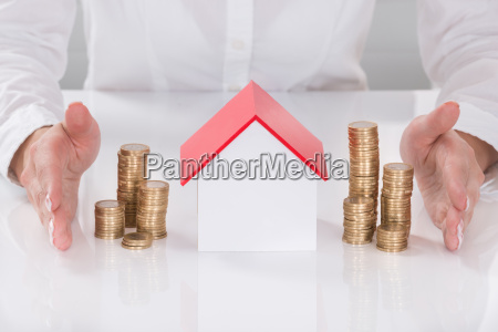 females hand protecting house model and